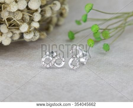 A Pair Of Beautiful Diamond Earrings In Infinity Shape On Gray Background