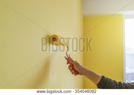 Workman Painting The Wall In Yellow.