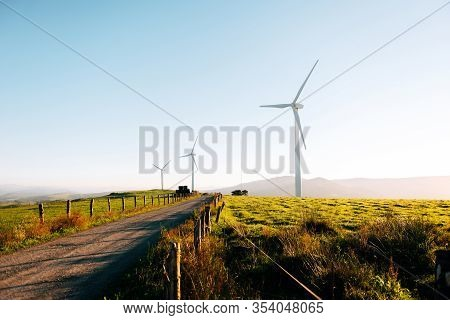 Wind Turbines On Beautiful Sunny Summer. Road Through Mountain Eolic Park. Green Ecological Power En