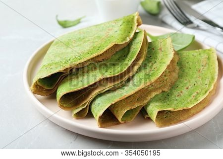 Tasty Spinach Crepes On Light Grey Table, Closeup