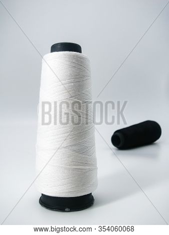 a bobbin with white sewing threads stands in the foreground. in the background is a bobbin with blac