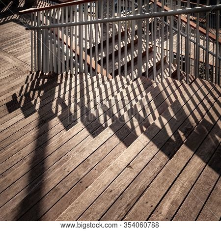 Staircase With A Shadow From The Railing. Close-up Of A Staircase Descending With Wooden Steps And M