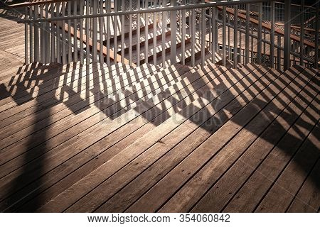 Staircase With A Shadow From The Railing. Close-up Staircase With Wooden Steps And Metal Railing. A
