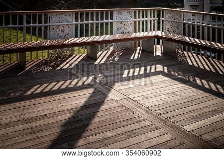 Staircase With Benches With A Shadow From The Railing. Staircase With Wooden Steps And A Shadow From