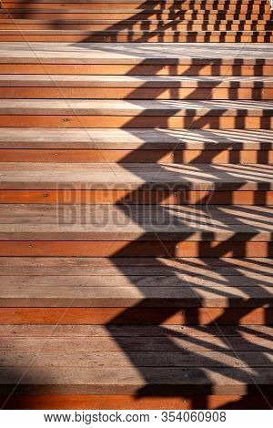 Staircase With Shadows From The Railing. Close Up Of A Staircase With Wooden Steps And The Shadow Of