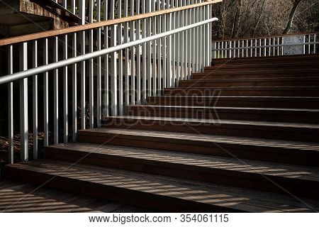 Staircase With A Shadow From The Railing. The Rising Staircase With Wooden Steps And Metal Railing.