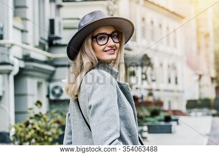 Back View Happy Beautiful Girl Looking To Camera And Smiling While Standing On City Street. Fashiona