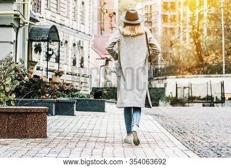 Back View Of Stylish Young Woman In Coat And Hat Keeping Hands In Pockets Walking Away On City Stree