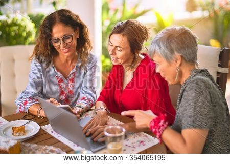 Meeting of middle age women having lunch and drinking coffee. Mature friends smiling happy using laptop at home on a sunny day