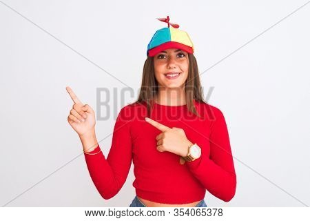 Young beautiful girl wearing fanny cap with propeller standing over isolated white background smiling and looking at the camera pointing with two hands and fingers to the side.