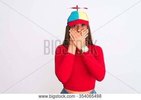 Young beautiful girl wearing fanny cap with propeller standing over isolated white background shocked covering mouth with hands for mistake. Secret concept.
