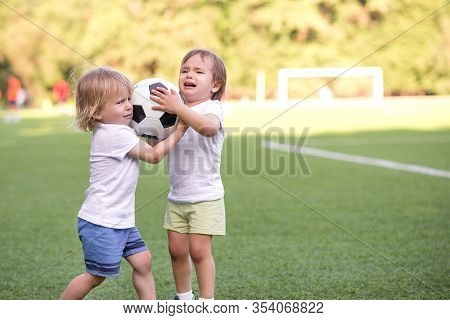 Two Little Toddlers Arguing At Football Field Or Playground Over Soccer Ball Trying To Take Or Grab