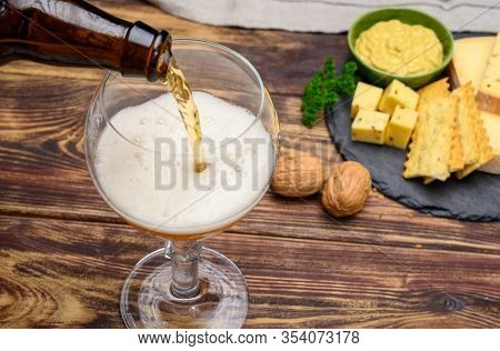 Pouring Of Belgian Abbey Blond Beer In Glass And Marble Plate With Cheeses Made By Monks From Cow Mi