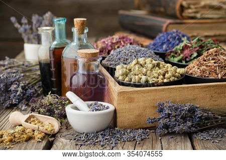Bottles Of Healthy Tincture Or Infusion, Mortar And Bowls Of Medicinal Herbs In Wooden Crate, Stack