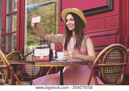 Love Making Selfie. Portrait Of Cute And Beautiful Smiling Woman In Pink Dress And Hat Taking Selfie