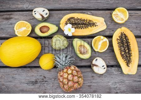Top View On The Wooden Table Full Of Exotic Fruits And Berries. Ananas, Papaya, Melon, Avocado, Oran