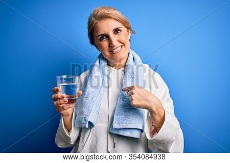 Middle age beautiful blonde sportswoman wearing towel drinking glass of water to refreshment with surprise face pointing finger to himself