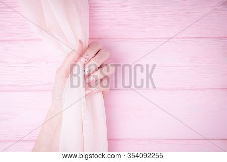 Beautiful Female Hand Holding Flowing Silk Fabric. Natural Manicure With Pink Color Nail Polish, Bla