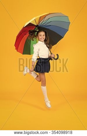 Back To School On September 1. Adorable Schoolgirl With Rainbow Umbrella On September 1 On Yellow Ba