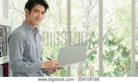 A 25-35 Year Old Asian Business Man Smiled Happily In The White Office. He Was Checking The Document