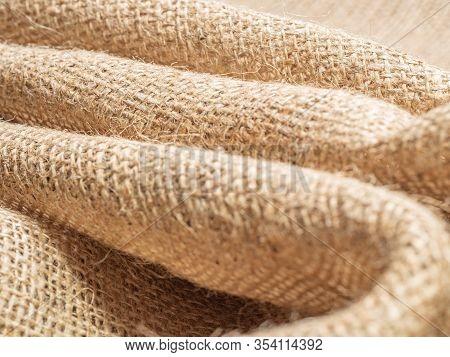 Brown Sackcloth. Crumpled Burlap Textile, Close Up View. Texture Of Brown Burlap. Crumpled Baline, A