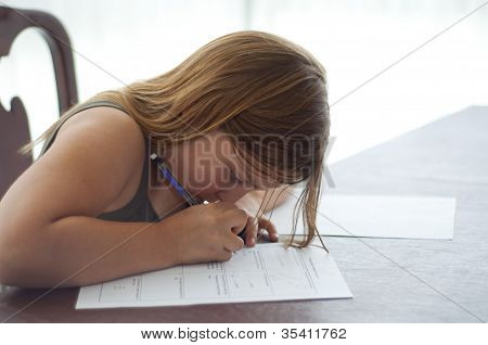 Young Girl Doing Homework At Kitchen Table