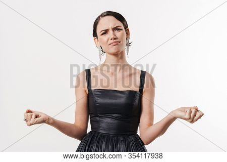 Attractive confused young brunette woman wearing black cocktail dress standing isolated over white background, shrugging shoulders