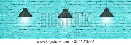 Hanging Pendant Lamps Against Turquoise Painted Brick Wall. Modern Industrial Interior Background