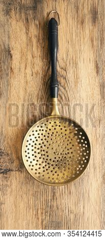 Old Used Skimmer On A Rustic Wooden Plank, Vintage Kitchen Tools