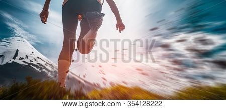 Young woman hiker runs on the trail with snow capped volcano on the background and rocks flying in the air on the foreground