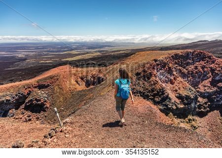 Galapagos tourist hiking on volcano Sierra Negra on Isabela Island. Woman on hike visiting famous landmark and tourist destination by active volcanic caldera, Galapagos Islands Ecuador