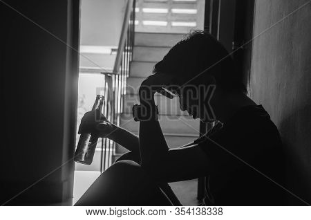 The Silhouette Of Young Men Holding A Bottle Of Alcohol Beer At The Old Condo, Unhealthy Lifestyle,
