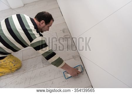 Grouting ceramic tiles. Tilers filling the space between ceramic wood effect tiles using a rubber trowel on the floor in new modern apartment
