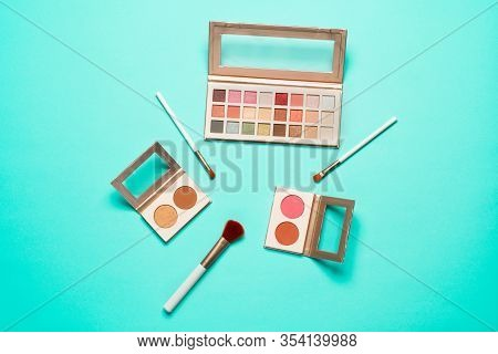 Makeup Brush And Cosmetics On Blue Background. Top View Point, Flat Lay.