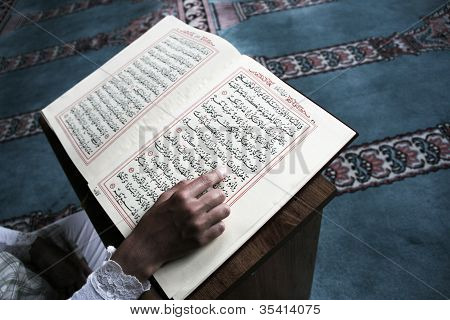 young muslim girl reading the Koran in mosque poster