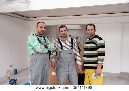 portrait of Workers and builders in uniform at apartment that is under construction, remodeling,renovation,extension, restoration, overhaul and reconstruction