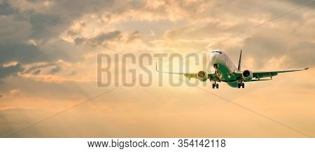 Passenger Airplane. Landscape With Front Of White Airplane Is Flying In The Orange Sky With Clouds,