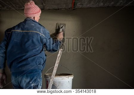 Construction worker plastering interior wall using cement plaster  Worker plastering the wall by concrete at the construction site