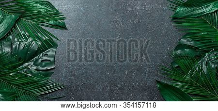 Palm Leaves On Dark Blue Background. Tropical Leaves Top View Or Flat Lay. Copy Space For Text Or De