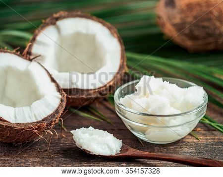 Liquid Coconut Mct Oil And Halved Coco-nut On Wooden Table. Health Benefits Of Mct Oil. Mct Or Mediu