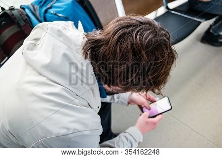Man Waiting For His Flight In The International Airport And Typing Message On Phone.