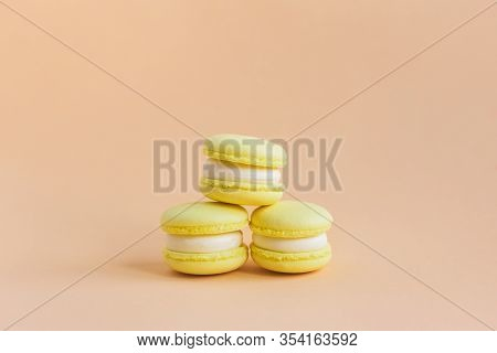 Yellow Macarons On A Peach Pastel Background. Lemon Macarons. Place For Text.