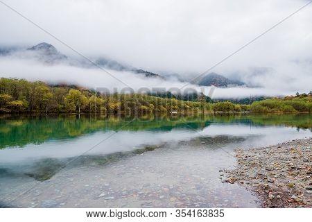 Lake Taisho Pond In Autumn With Foothill Fog Along Hotaka Mountain Range In Kamikochi National Park,
