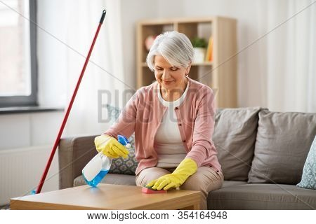 household and people concept - happy senior woman with detergent and sponge cleaning table at home