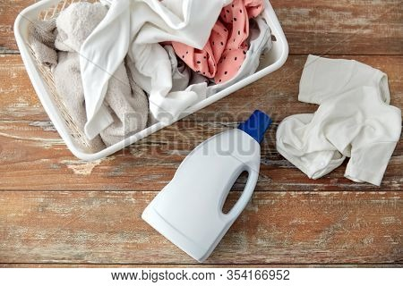 laundry, wash and housekeeping concept - baby clothes in basket with detergent or conditioner bottles on wooden table at home