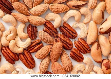 Pattern Of Assorted Nuts Pecans, Macadamis, Brazil Nut, Cashews, Almonds On A Gray Background. Top V