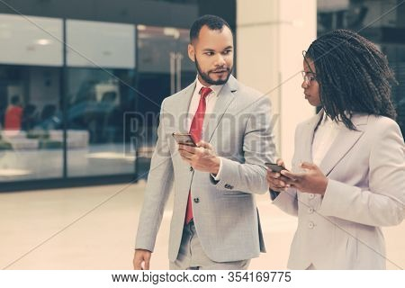 Excited Business Colleagues Using Mobile Phones On Their Way To Office. Business Man And Woman Walki