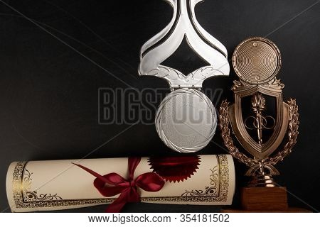 Golden trophy and certificate over blackboard background. top view. flat lay.Trophy is a specific achievement, serves as recognition / evidence of merit, awarded for sporting events