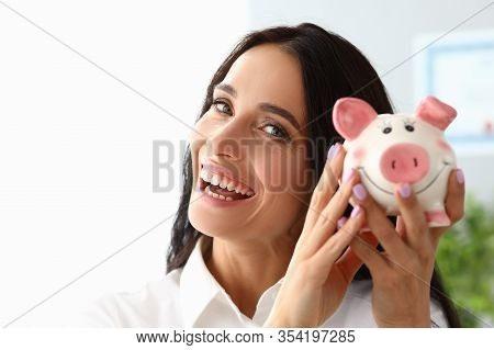 Beautiful Woman Shows Piggy Bank And Smiles. Selection Suitable Items In Stores From Customers Price