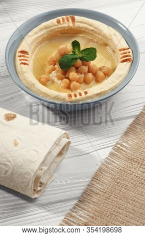 Top View Of Arabic Hummus And Wrapped Bread And Hessian Sack On White Table